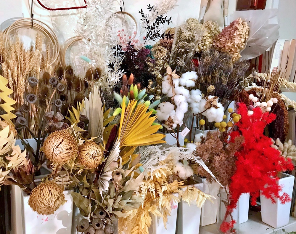 Tightly packed white vases of dried flowers and foliage