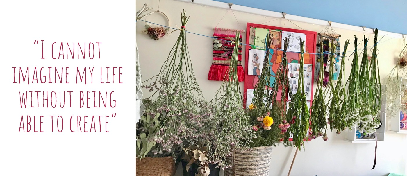Bunches of flowers hanging upside down to dry across Cristelle's home studio with a selection of weavings, floral art and drawings in the background: 'I cannot imagine my life without being able to create'