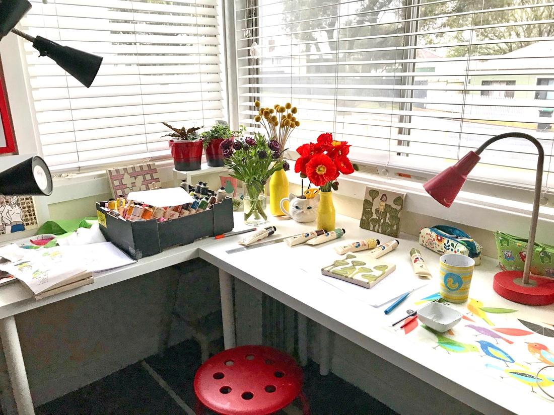 Cristelle's colourful, sun-drenched studio desk covered in paints, papers, flowers and works in progress