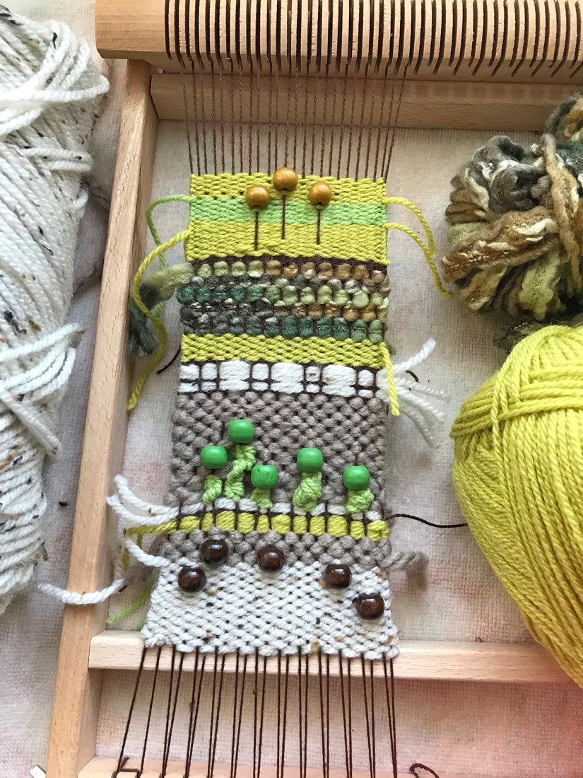 A lime green and neutral beaded weaving in progress on Cristelle's loom
