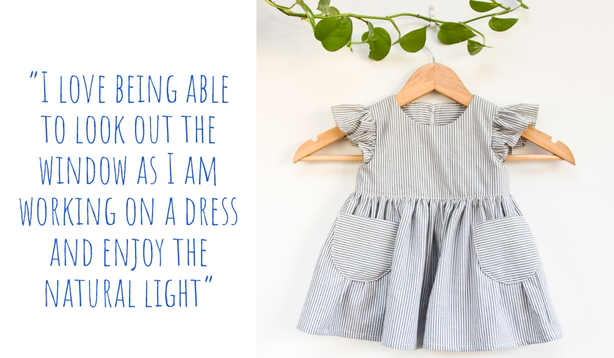 Sustainable handmade flutter-sleeve toddler dress with pockets in white and grey pinstripe; 'I love being able to look out the window as I am working on a dress and enjoy the natural light'