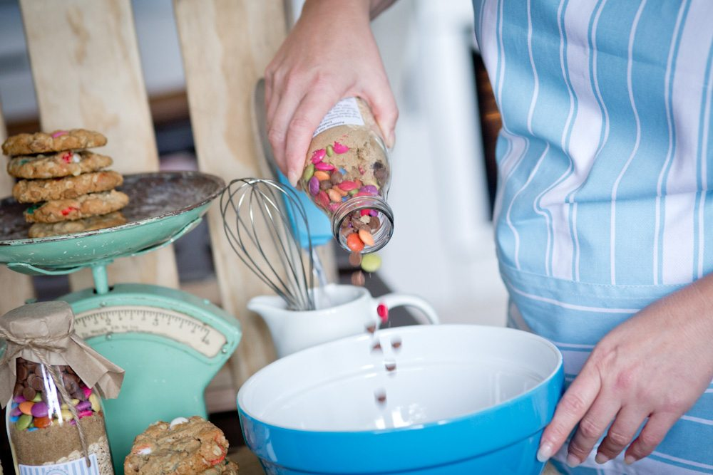 Pouring a Sweet Health cookie mix into a mixing bowl with cookies in the background