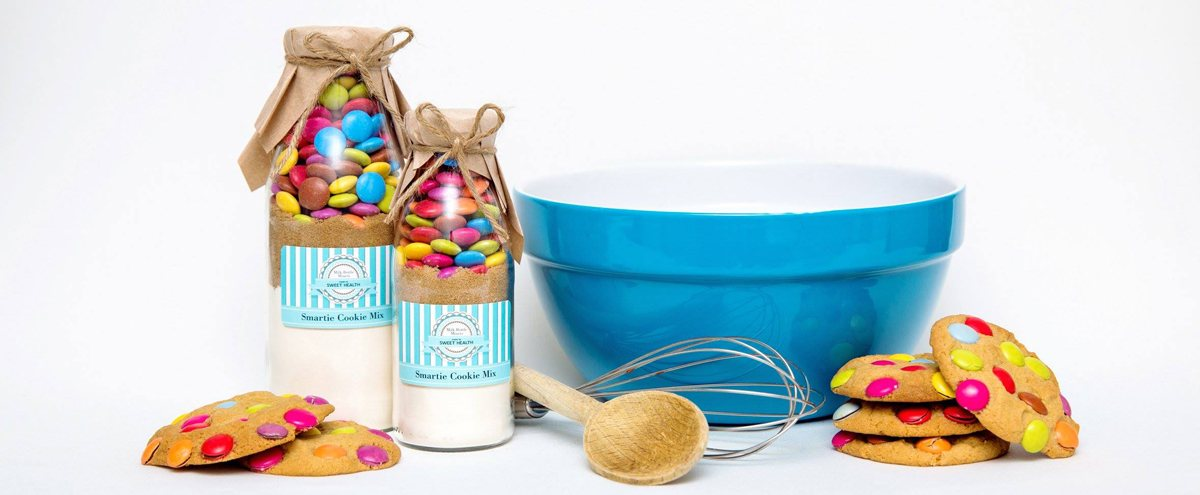 Smart Cookie cookie mixes in vintage style bottles with baking implements and some deliciously colourful cookies