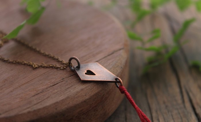Copper kite pendant with heart cut-out and red tassel
