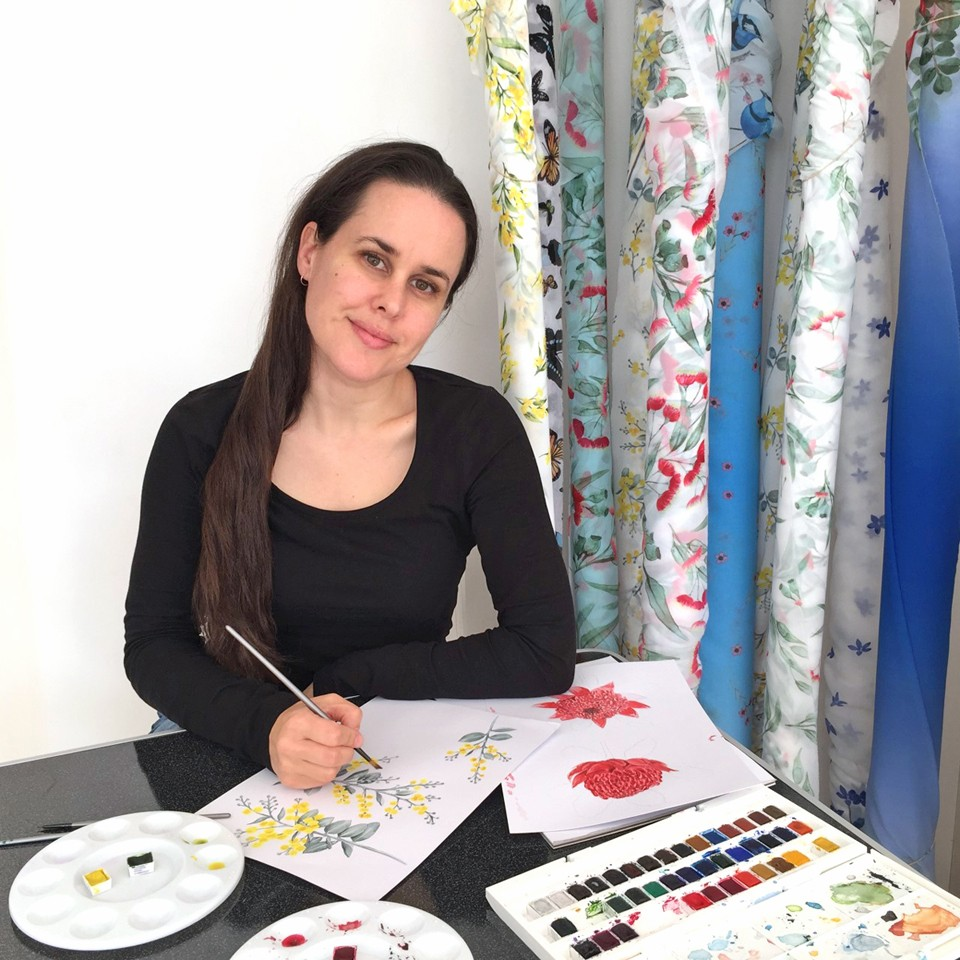 Shelley at work painting more watercolour designs for her products, with a backdrop of her past fabric range
