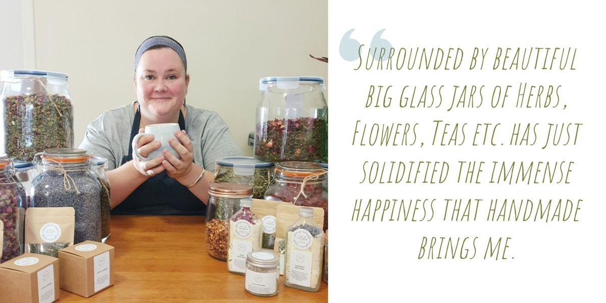 Alyssa nursing a large cup of tea in her happy place, surrounded by jars of herbs and some of her product range; 'Surrounded by beautiful big glass jars of herbs, flowers, teas etc. has just solidified the immense happiness that handmade brings me