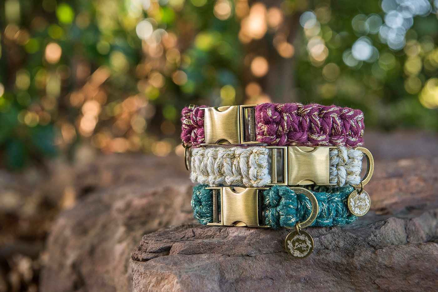 A stack of The Boho Pet macramé dog collars in three metallic shades