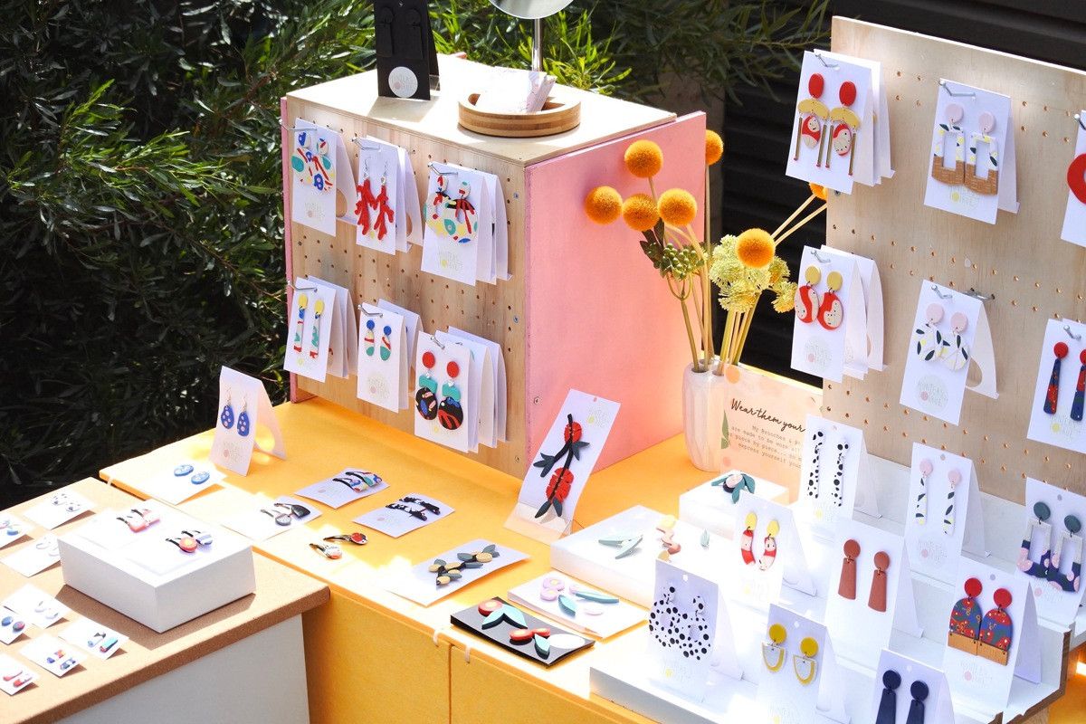 A bright and colourful market display of The Hunters True earrings, brooches and hair clips
