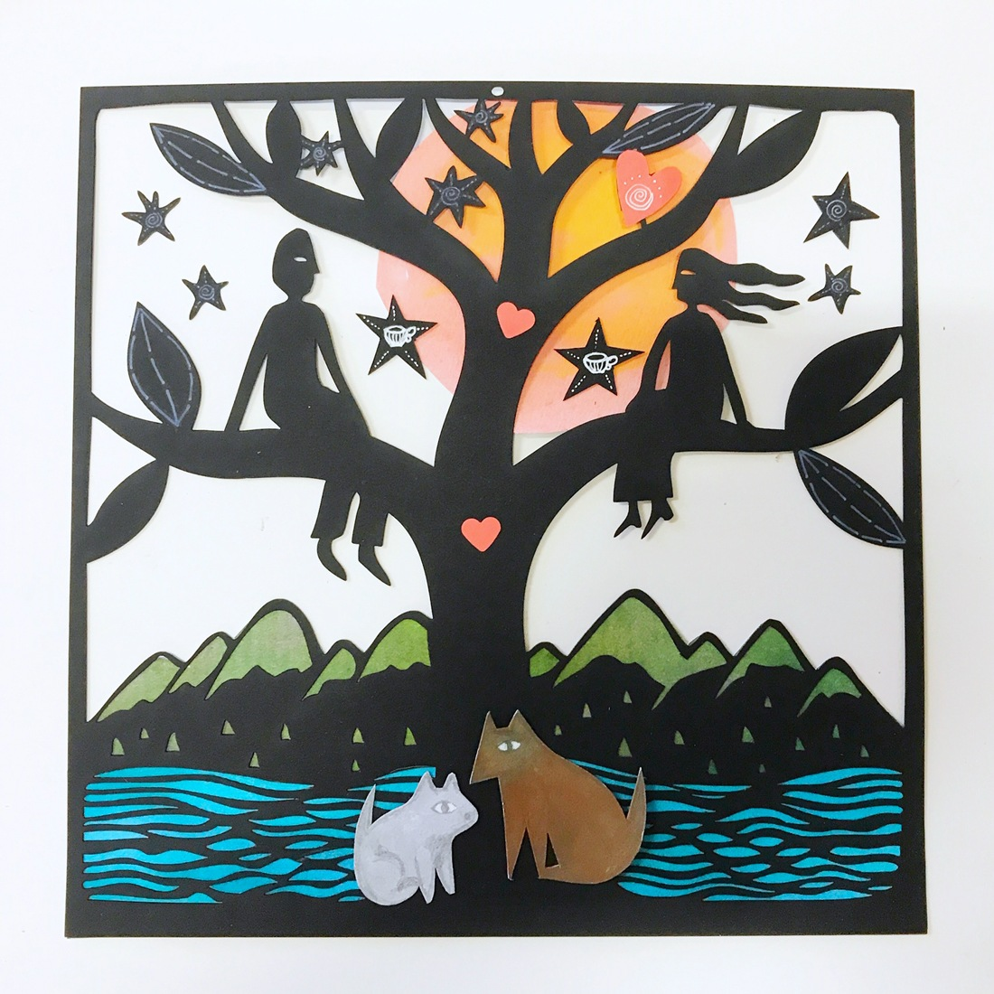 A more colourful work than Sue's usual monochrome, this papercur piece depicting a couple in a try with the sunset and mountains in the background and a cat and dog at the bottom of the tree with a vibrant blue river flowing past