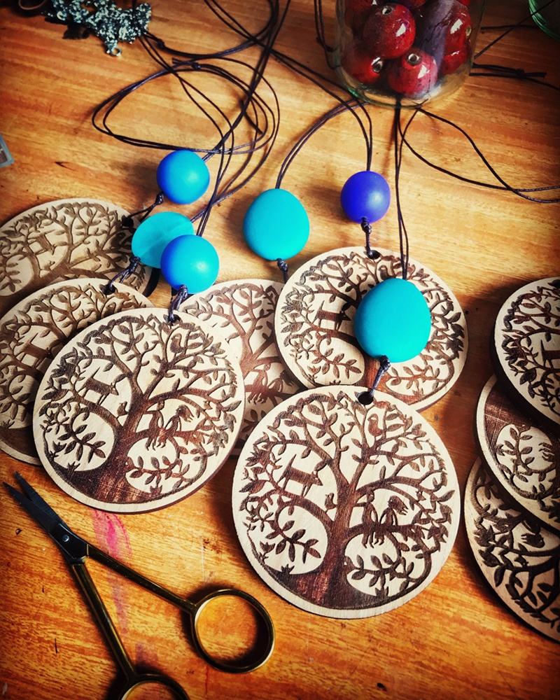 A collection of lasercut timber pendant necklaces awaiting completion on Sue's work bench