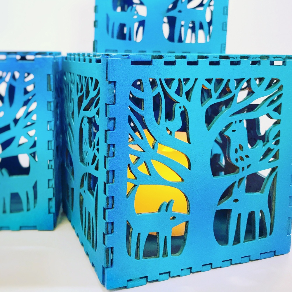 A stack of blue lasercut lightboxes featuring animals in trees in Sue's signature style