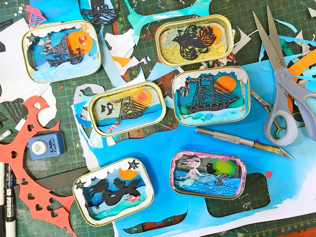 A series of small works in progress – 3-dimensional layered papercut scenes in sardine tins