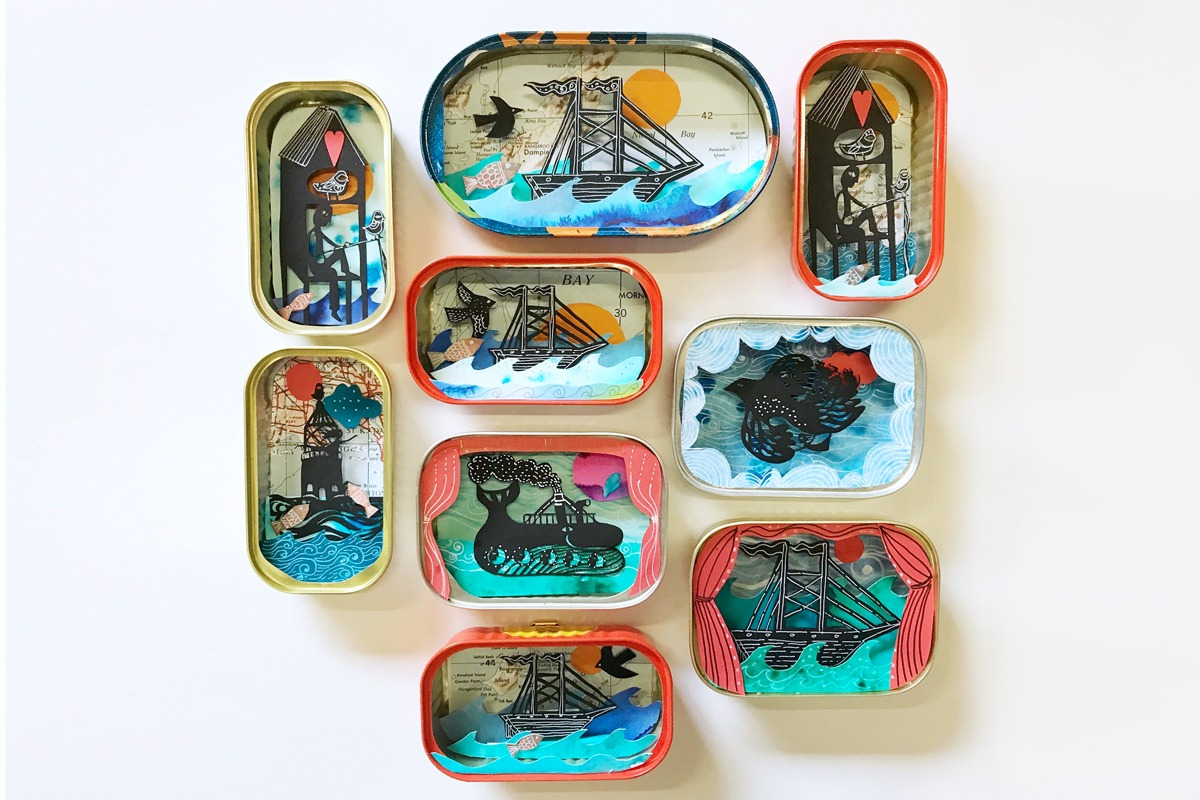 A collection of finished tiny 3-dimensional papercut nautical themed artworks layered into sardine tins