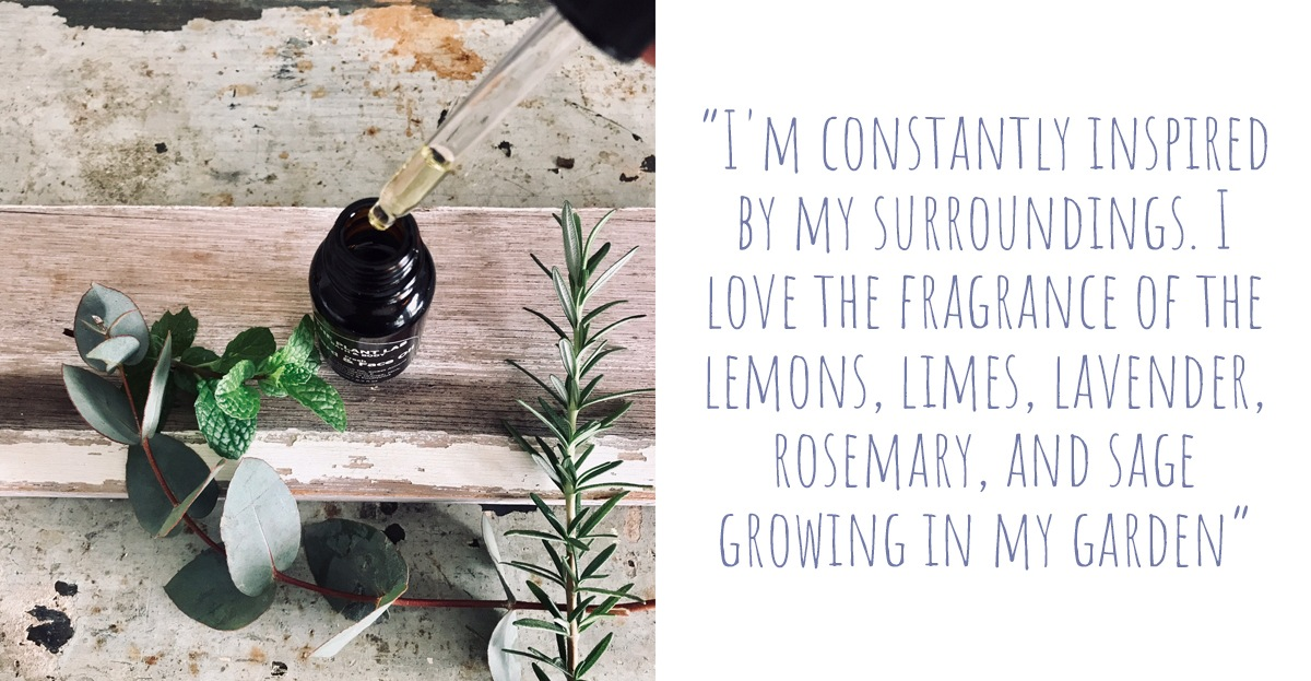 An eye-dropper bottle of natural skincare oils on a timber bench surrounded by sprigs of Eucalypt, fresh mint, and rosemary; 'I'm constantly inspired by my surroundings. I love the fragrance of the lemons, limes, lavender, rosemary, and sage growing in my garden'