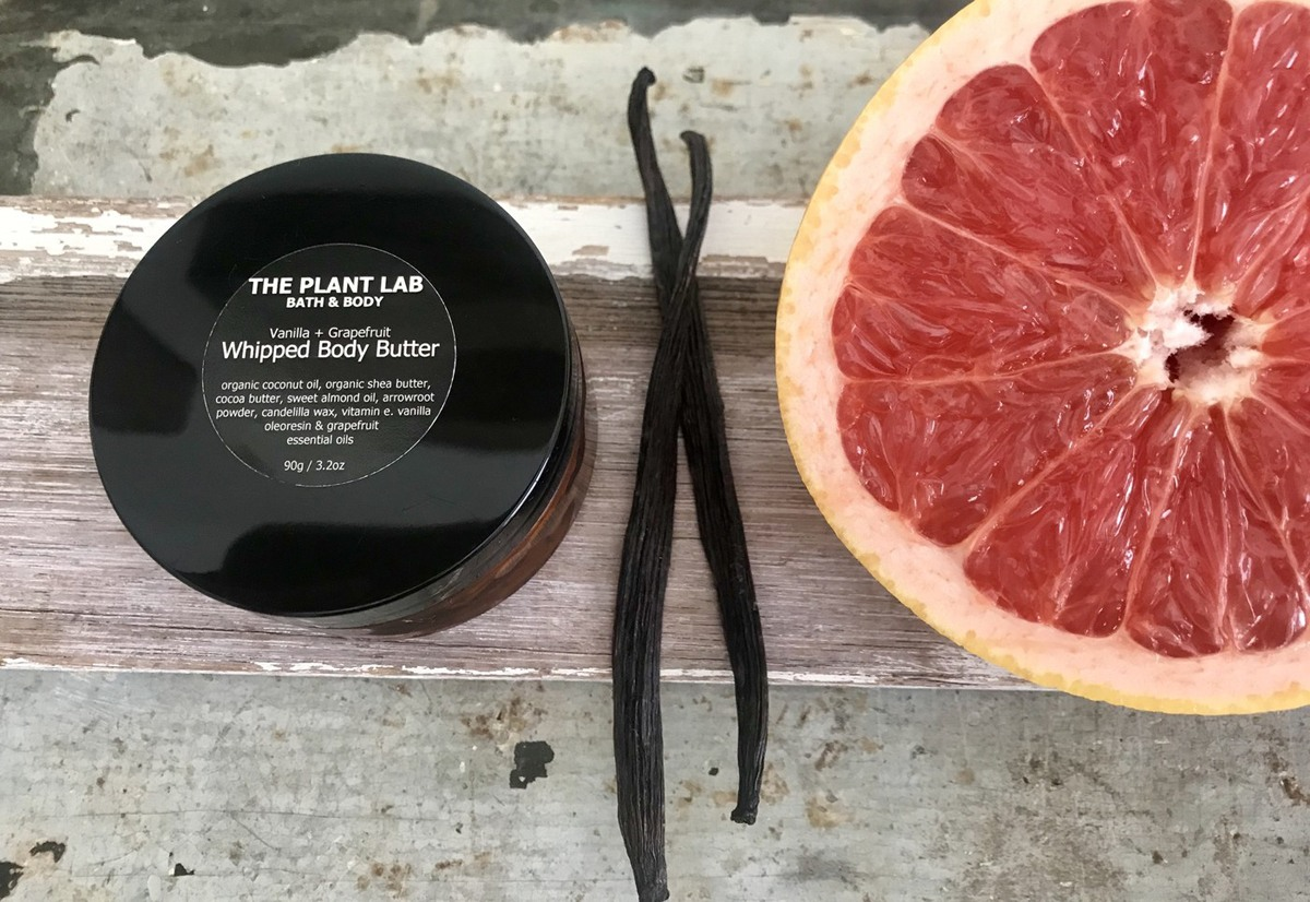 A pot of Vanilla & Grapefruit whipped body butter by The Plant Lab Bath & Body on a timber bench with some vanilla beans and half a grapefruit