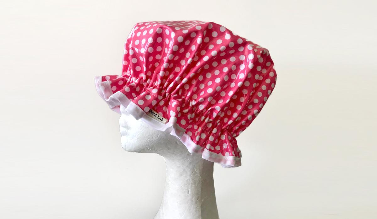 A foam dummy wearing a red and white polka dot laminated cotton shower cap handmade by The Plant Lab Bath & Body