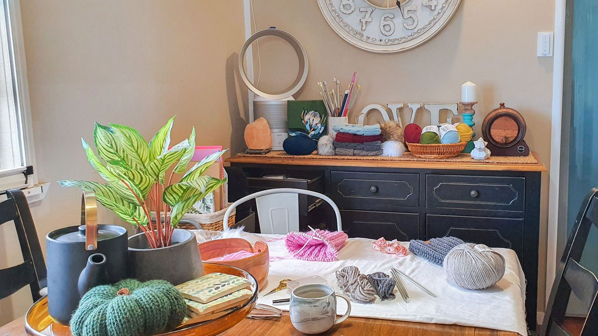 Victoria's home workspace: skeins of yarn, knitting needles, works in progress and finished pieces adorn the family dining table and buffet of Victoria's small Queenslander in Childers