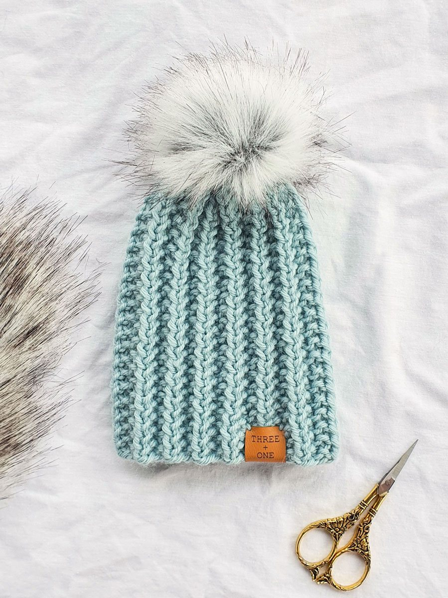 A chunky textured beanie in seafoam blue with fluffy pompom and tan leather Three + One label'