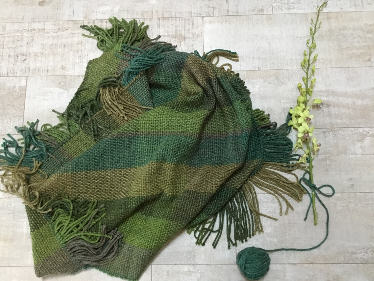 Hand-woven blanket in shades of green by Tall Tree Weaves