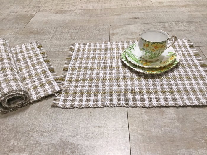 A fine china teacup setting on some Tall Tree Weaves hand-woven placemats