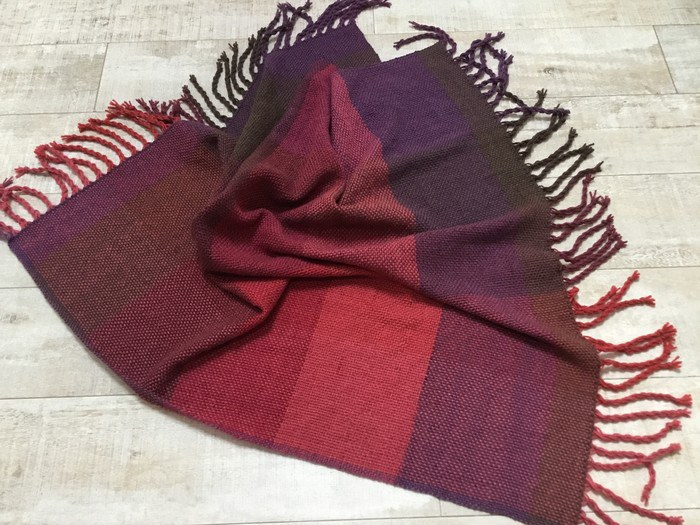 A handwoven acrylic and woollen throw in red and plum hues by Tall Tree Weaves