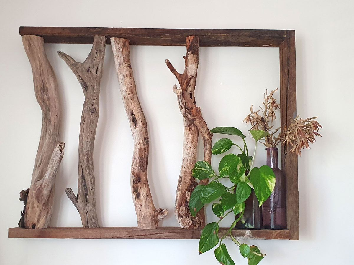 Even an art piece Ric created for his home from driftwood pieces collected at local beaches serves some function as a shelf