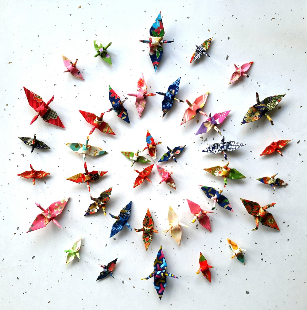 Aerial photo of concentric circles of very tiny paper cranes by Wish Upon A Wing