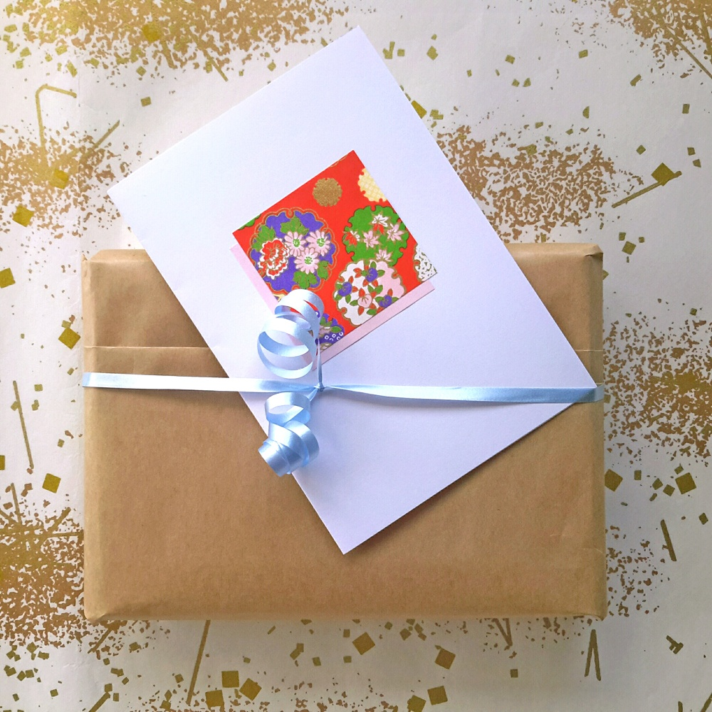A Wish Upon A Wing order ready to post, neatly gift wrapped in brown paper, simple baby blue ribbon, and handmade card with vibrant red origami paper feature